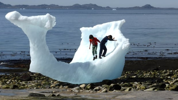 Children play amid icebergs on the beach in Nuuk, Greenland, on June 5. A new study suggests three square metres of Arctic sea ice disappears for every tonne of CO2 produced by humans.