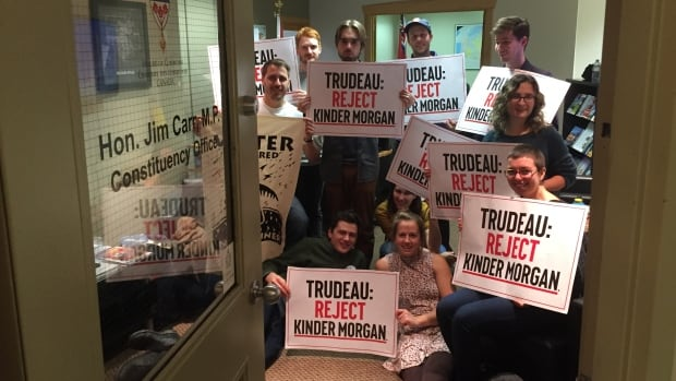 A dozen people occupied M.P. Jim Carr's office in Winnipeg on Thursday. They want him to reject Kinder Morgan's proposal to expand the Trans Mountain pipeline.