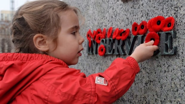 A child places a poppy on the National War Memorial following the Remembrance Day ceremony in Ottawa last year.