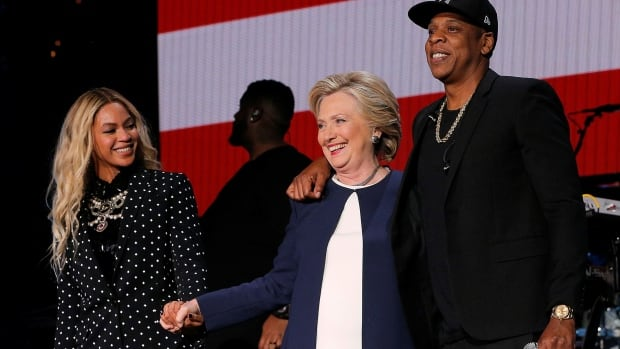 U.S. Democratic presidential nominee Hillary Clinton joins Jay Z, right, and Beyoncé, left, onstage at a campaign concert in Cleveland, Ohio, on Friday.