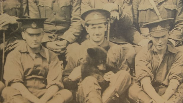 A photo of, enlarged to life-size, at the Remembering the Real Winnie exhibit shows little Winnie snuggled in with members of the Canadian infantry.