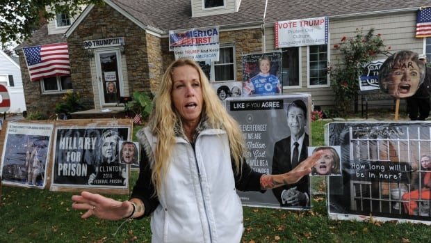 Eileen Fuscaldo stands outside her home Bellmore, N.Y., which features a collection of pro-Donald Trump and anti-Hillary Clinton signs.