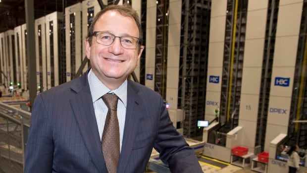 Hudson Bay's CEO Jerry Storch stands in front of the company's new robotic fulfillment system in Toronto
