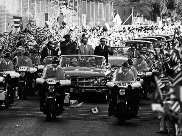Thousands of Cuban people line the streets in Havana to greet Trudeau as he drives through the city in January 1976. Castro is with him in the open car.
