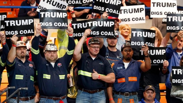A group of coal miners wave signs for Donald Trump as they wait for an election rally in Charleston, W.Va.