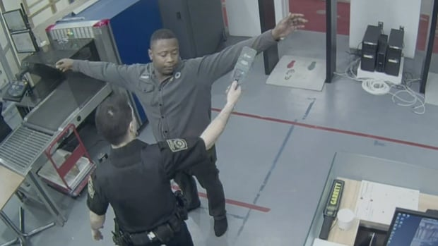 A still image from a surveillance video shows Leston Lawrence being checked by a guard with a hand-held metal detector at the Royal Canadian Mint in Ottawa on Feb. 2, 2015. On Thursday, Lawrence was given a 30-month prison sentence for smuggling 22 solid gold 'pucks' out of the mint and selling some of them.