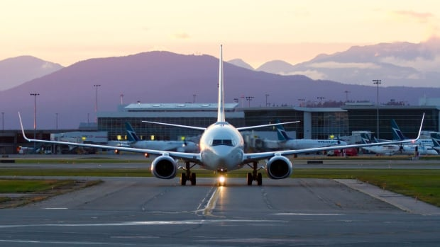 A Boeing 737 airplane at YVR preparing to take off at sunset.