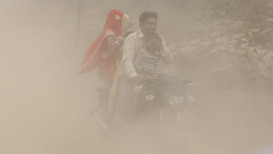 An Indian man and his family ride a bike during heavy dust and smog in New Delhi, India, Nov. 6, 2016. A thick grey haze enveloped India's capital as air pollution hit hazardous levels.