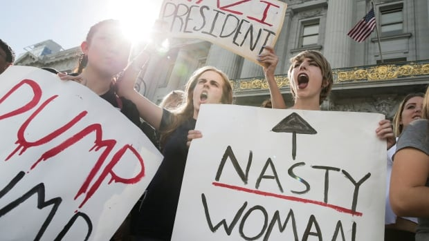 Young women protest against the election of Donald Trump as U.S. president. Feminist economists says work traditionally done by women isn't counted in national accounts.