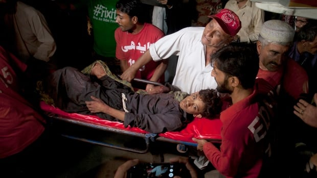 Pakistani rescue workers and volunteers carry an injured victim of a bomb blast at a Sufi shrine.