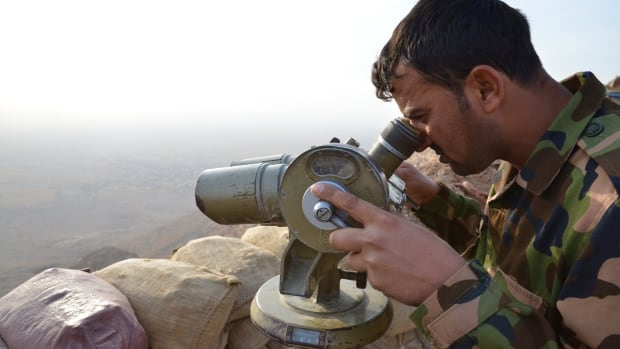 A Kurdish soldier looks out for ISIS fighters at the front on Zardek Mountain, northwest of Erbil.