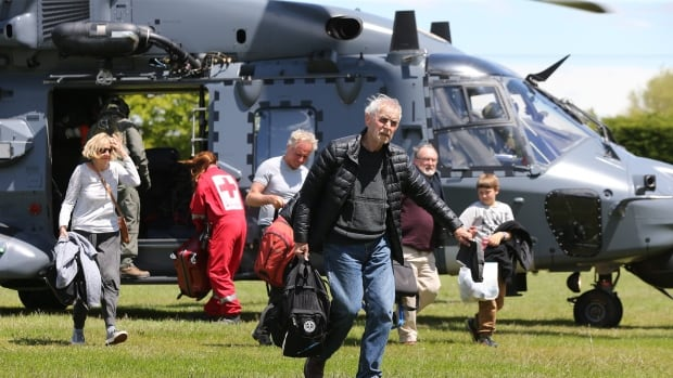 Tourists trapped by the Kaikoura earthquakes arrive by military helicopters at Woodend School grounds on Tuesday in Christchurch, New Zealand after the major earthquake two days earlier left them stranded.