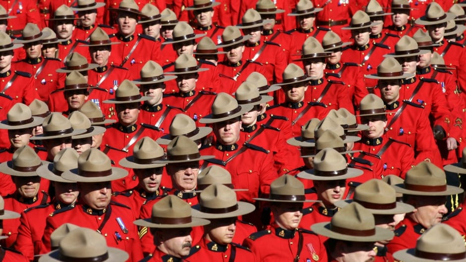 Royal Canadian Mounted Police officers march during a memorial for four slain officers in Edmonton, Alberta, in this March 10, 2005 file photo. The head of the troubled RCMP admitted on December 14, 2007 that the national force needed a major overhaul to deal with a widespread lack of morale, scarce resources and heavy public criticism.     REUTERS/Shaun Best             (CANADA) - RTX4QVH