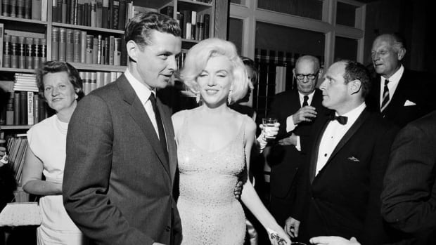 Marilyn Monroe wears the iconic gown that she wore while singing Happy Birthday to U.S. President John F. Kennedy at Madison Square Garden, during a reception in New York City on May 19, 1962. Standing next to Monroe is Steve Smith, Kennedy's brother-in-law.
