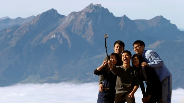 Mount Pilatus is seen behind the fog as a group of tourists takes a selfie on the peak of Mount Rigi, Switzerland at 1,797 m above sea level on Oct. 16, 2016.