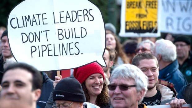 A woman holds a sign during a protest and march against the Kinder Morgan Trans Mountain Pipeline expansion in Vancouver on Saturday. Ottawa will make a decision on the controversial project in the next 30 days.
