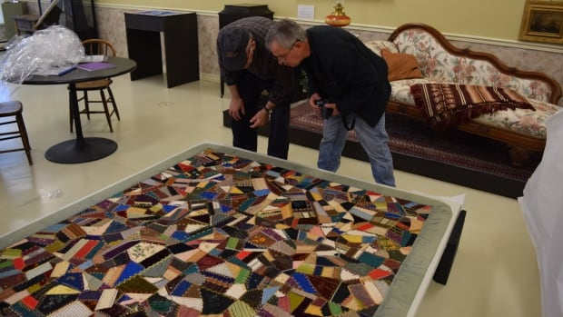 Richard Brown, right, former president of the Kings County Historical Society, examines the newly revealed quilt with another society member.