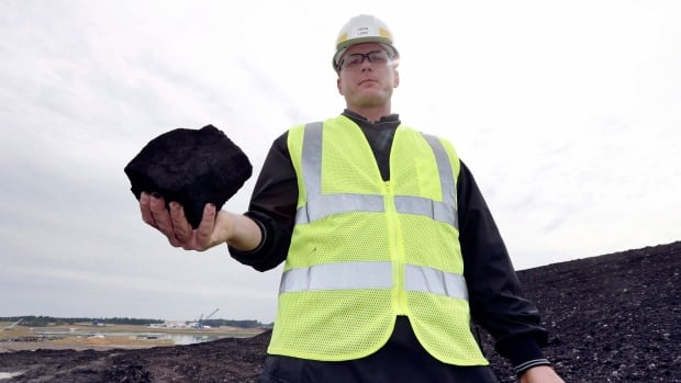 A worker holds a piece of coal destined for a coal-fired power plant. The federal government announced plans Monday to take the country's coal plants offline by 2030, which is expected to result in a reduction of roughly 61 megatonnes of annual emissions.