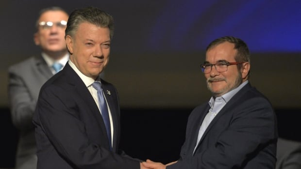 Colombian President Juan Manuel Santos, left and the head of the FARC guerrilla Timoleon Jimenez, aka Timochenko, shake hands during the second signing of the historic peace agreement in Bogota on Nov. 24, 2016. The deal took years to negotiate.