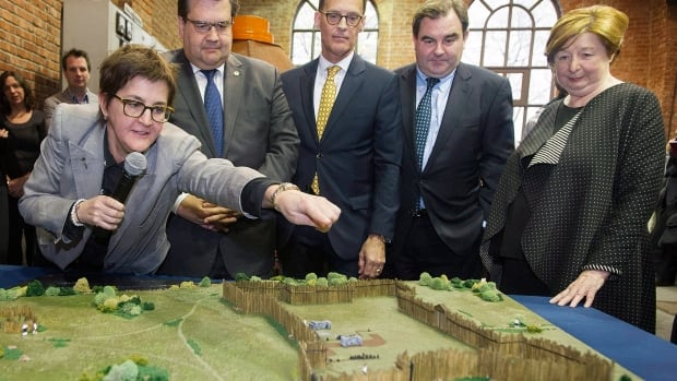 Archaeologist Louise Pothier, left, points to a scale model of Fort Ville-Marie to, from left, Montreal Mayor Denis Coderre, J.Serge Sasseville from Quebecor, Pointe-à-Callière Museum Chair of the Board Andrew Molson and museum executive director Francine Lelievre.