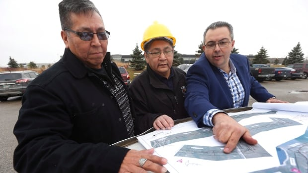 From left, Daryl Redsky, consultation officer, Chief Erwin Redsky, both of Shoal Lake 40 First Nation, and Phil Cesario, design project manager at PM Associates Ltd. go over the final design drawings for Freedom Road, an all-weather road which will connect the reserve to the Trans Canada highway.