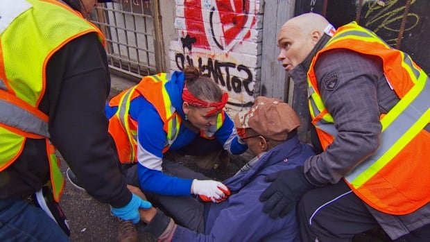 Volunteers with one of the city's pop-up injection sites respond to a man who has overdosed in an alley on Vancouver's Downtown Eastside.