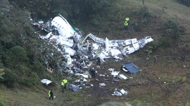 Police officers and rescue workers search for survivors around the wreckage of a chartered airplane that crashed in Colombia late last month.