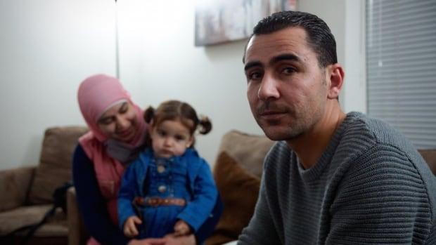 Shadi al-Radi sits in his living room with his wife Saja Ayyash and their toddler Zain.