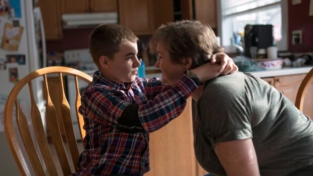 Sean Bellefeuille, 13, embraces his mother Dawn at their home in Ottawa.  It wasn't until his parents started giving him a high-CBD, low-THC cannabis oil that the number of their son's daily seizures dropped dramatically.