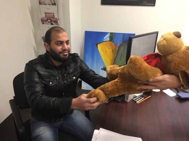 Fath Elbab handed a cuddly toy to Dada for his two year old son