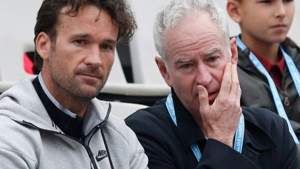 Carlos Moya, left, with John McEnroe at the French Open this past May, were part of Milos Raonic's coaching staff.