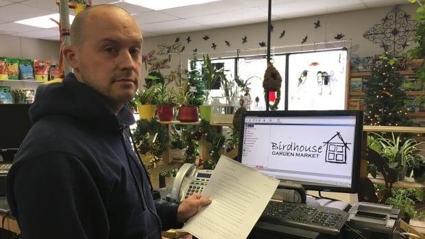 Bernard Bird stands in front of a cash register. It's one of five computers in his network hit by a ransomware attack.
