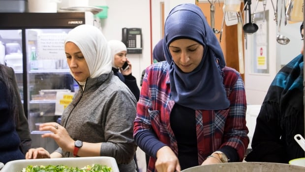 Lena Al Ahmad, right, and other Syrian refugee women prepare food for a multicultural dinner at the Mount Pleasant Neighbourhood House on Saturday Dec. 3, 2016 in gratitude for the support they have received in settling as newcomers in Vancouver.