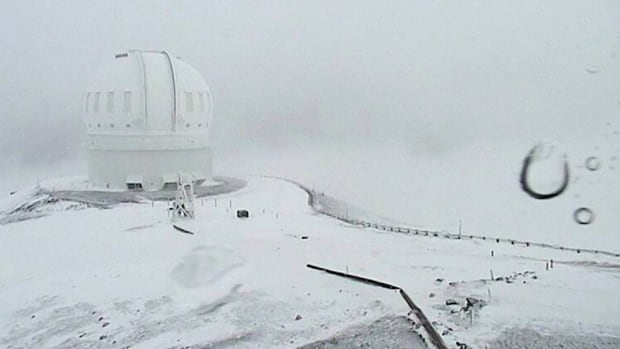 In this image made from webcam video taken on Dec. 1, snow blankets the summit of Mauna Kea on Hawaii's Big Island.