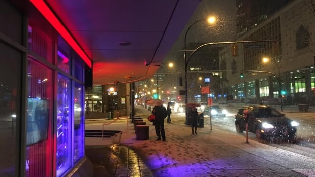The snow was sticking to the roads and sidewalks in downtown Vancouver on Monday morning.