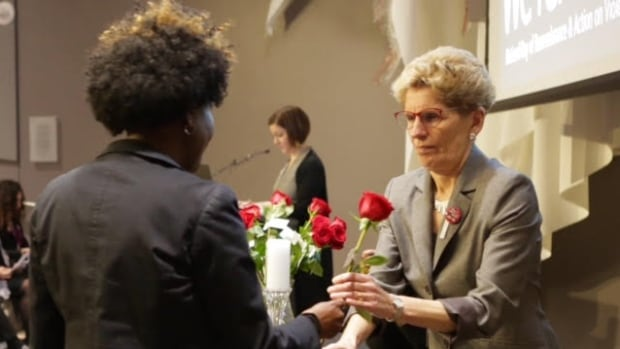Ontario Premier Kathleen Wynne takes a rose in memory of one of the 14 women killed at l'École Polytechnique on Dec. 6 in 1989.
