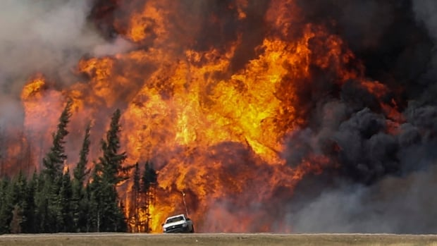 Smoke and flames from the wildfires can be seen behind a car on a highway near Fort McMurray, Alta.