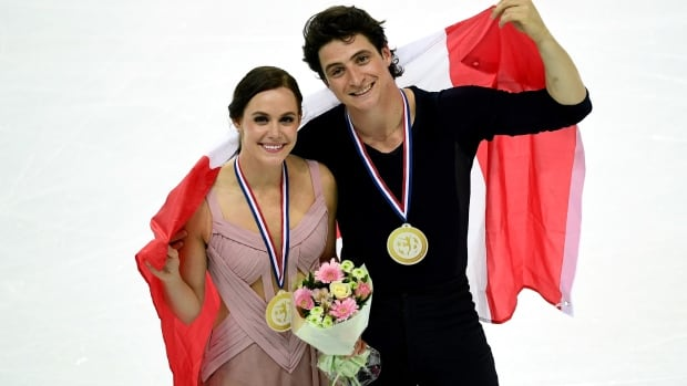 Tessa Virtue and Scott Moir pose with the Canadian flag and their gold medals as they celebrate after winning the ice dance Grand Prix of Figure Skating Final in Marseille, France, on Saturday.