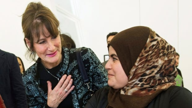 Quebec Immigration minister Kathleen Weil, left, talks with Syrian refugee Faten Nseirat during an event to mark the one-year anniversary of the arrival of refugees from Syria to Canada.