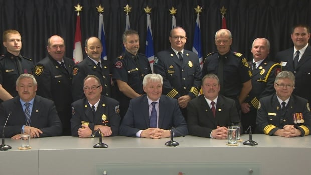 Firefighters pose with Service NL Minister Eddie Joyce (front-centre) after Monday's announcement.