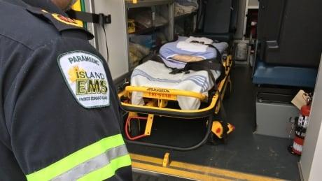 Island EMS ambulance paramedic looking inside van with stretcher