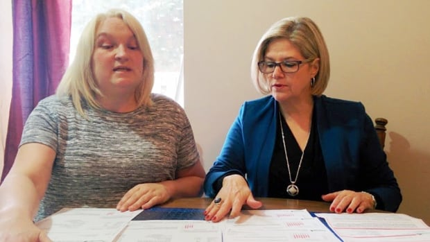 Adele Benoit, left, shows Ontario NDP Leader Andrea Horwath her hydro bills over recent months. Benoit says her bill has nearly doubled since the same time last year.