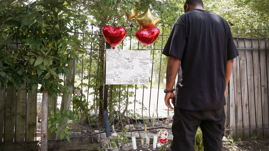 A Chicago man looks over a memorial for his friend who was shot and killed this summer. This has been the city's deadliest year in two decades.