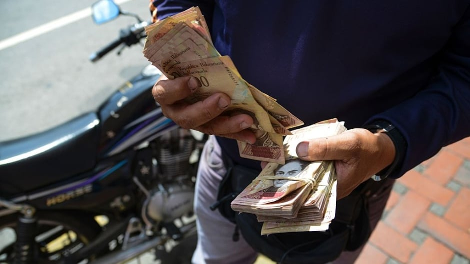 "A man counts 100 Bolivar bills on the street in Caracas. Venezuelan President Nicolas Maduro signed an emergency decree ordering the country's largest banknote be taken out of circulation to thwart ""mafias"" of hoarding cash."