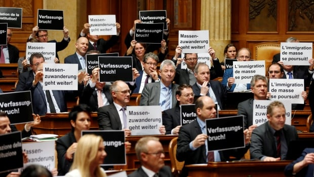 National Councilors of the Swiss People's Party hold posters reading 'constitutional breach' and 'mass immigration continues' after the vote on curbing the immigration in Bern.