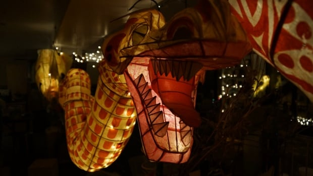 A large lantern in the shape of a dragon is suspended in the production space of the Secret Lantern Society. The organization is being evicted from the space to make way for a condo development.