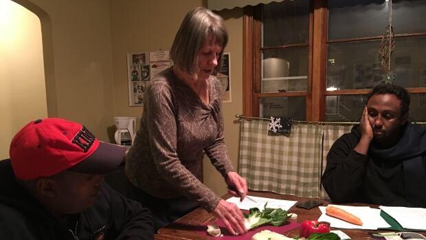 Asdedom Haile Tesfay, left, Mary Jane Eason and Abdi Rahman Ahmed prepare a stir-fry.