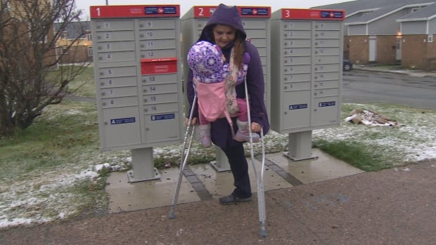 Using crutches and a baby carrier, Sydney Learning is able to check her mail and do all the other daily chores she needs to.