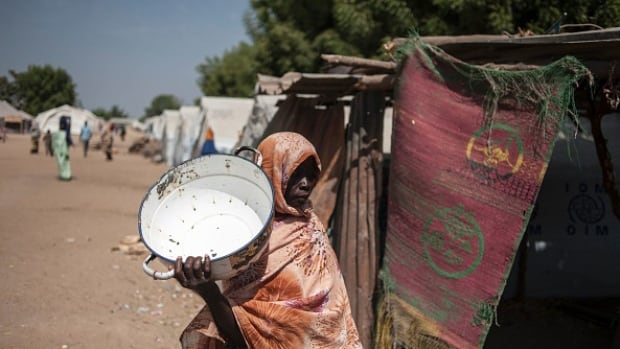 A woman visits a food distribution point at a camp for internally displaced people in the town of Bama, most of which was destroyed by Boko Haram jihadists. A new report from food security experts says a famine likely occurred in Bama and another town, Bamki, this year.