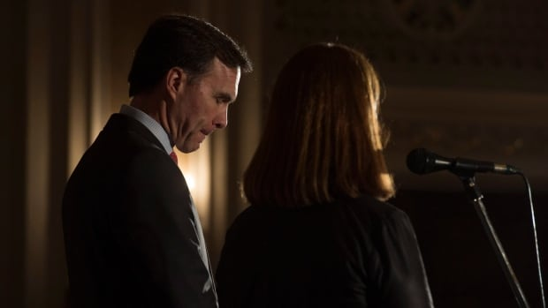 Finance Minister Bill Morneau bows his head during a news conference with Minister of Health Jane Philpott following the finance ministers meeting in Ottawa, Monday, Dec. 19, 2016.